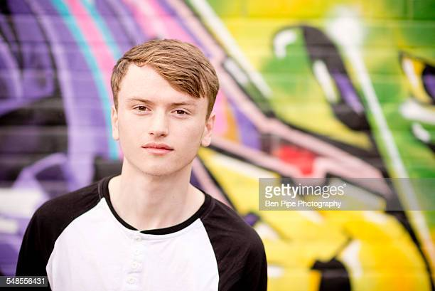 Teenager standing against wall with graffiti