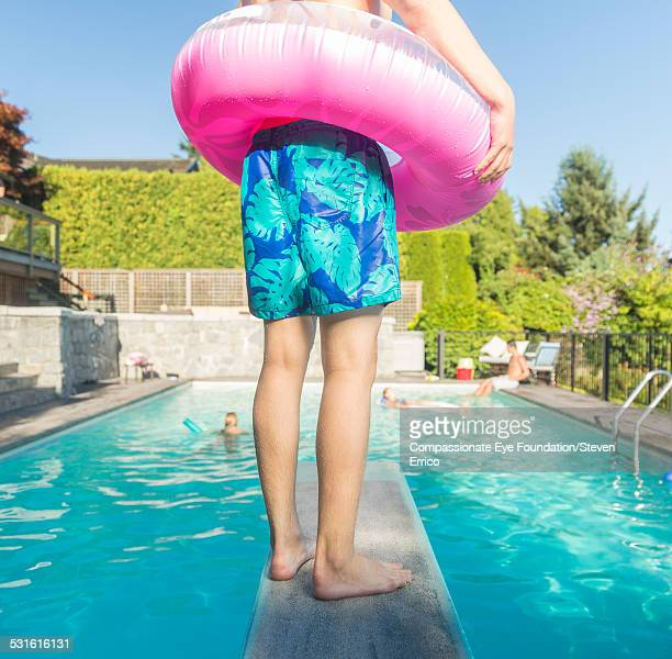Teenager standing on diving board with rubber ring
