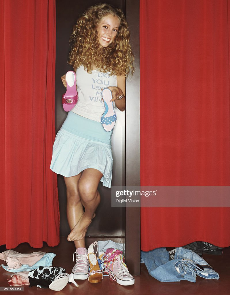 Teenager Standing on One Leg Holding Shoes in a Clothes Shop Fitting Room : Stock Photo