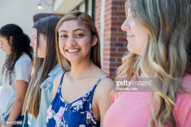 teenager standing with diverse group of friends - female high school student stock pictures, royalty-free photos & images