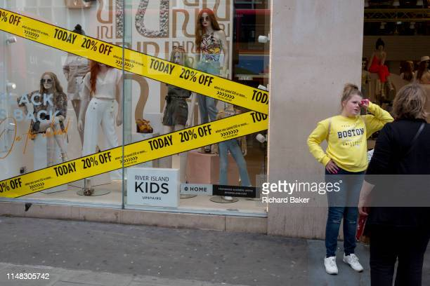 A teenager stands next to a shop promising 20% discounts on Oxford Street on 30th May 2019 in London England