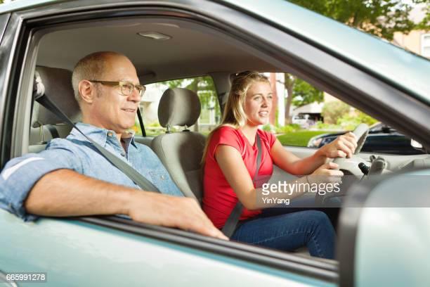 Adolescente estudiante conductor conduce con adulto, padre o padre en el asiento del pasajero
