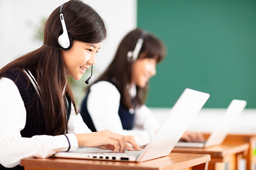 teenager student learning online with headphones and laptop 990711292