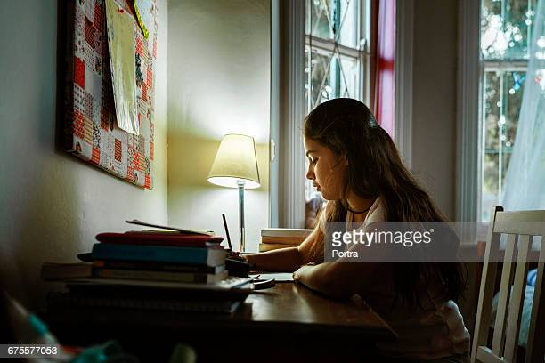 Teenager studying by illuminated lamp at table
