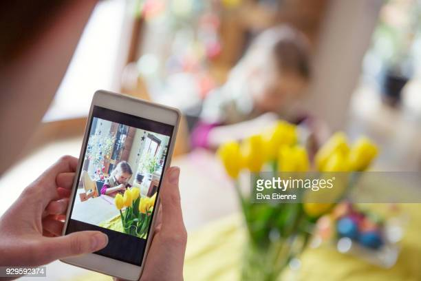 teenager taking a photograph on a mobile phone of another child painting easter crafts at a dining table - easter flowers stock pictures, royalty-free photos & images