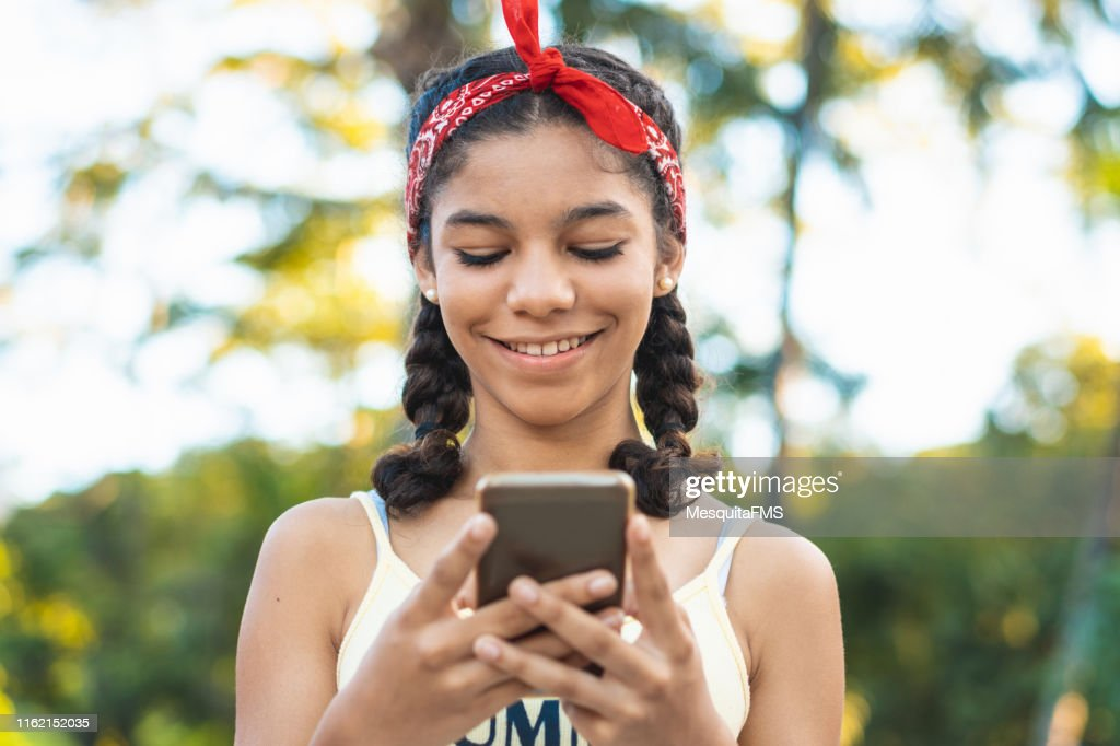 Teenager texting a message on smart phone : Stock Photo