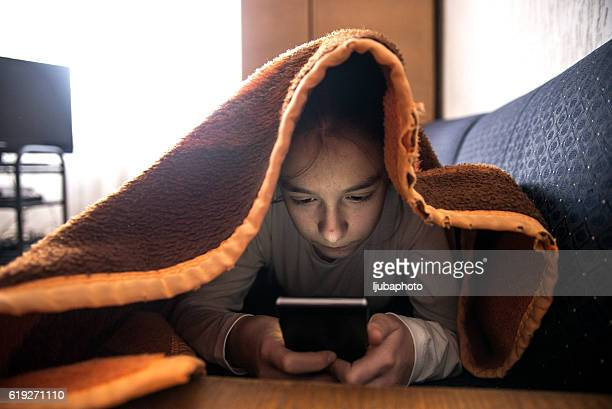 Teenager texting on smartphone at her living room