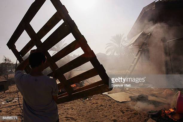 A teenager throws a wooden crate into a trash fire in front of a settler's home on August 17 2005 in the Israeli settlement of Neve Dekalim in the...