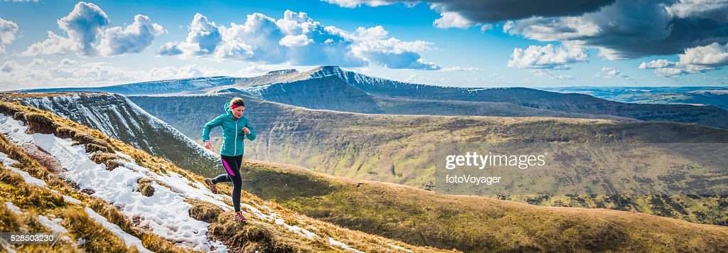 Teenager trail running along mountain path Brecon Beacons panorama Wales : Stock Photo