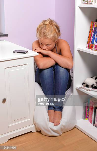 teenager upset by bullying on phone - online bullying stock pictures, royalty-free photos & images