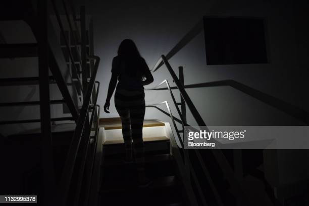 A teenager uses the light from a cellphone to climbs the stairs during a power outage at a home in the Palos Grandes district of Caracas Venezuela on...