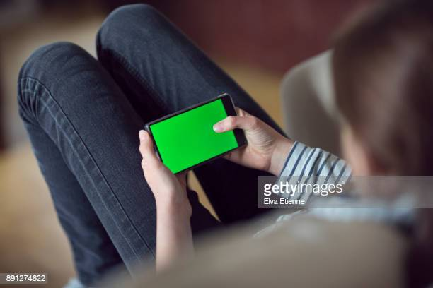 Teenager using a mobile phone with a green screen
