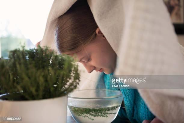 teenager using herbal steam inhalation as a remedy to treat respiratory symptoms of cold and flu virus - lichaamsverzorging en schoonheid stockfoto's en -beelden