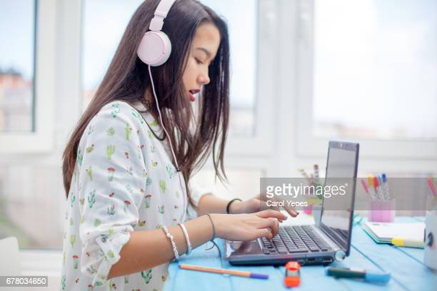 teenager using laptop with headphones