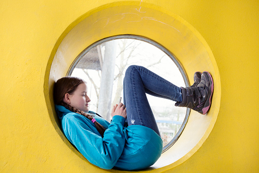 Teenager using mobile phone and lying down with feet up in the frame of a circular window in a yellow wall - gettyimageskorea
