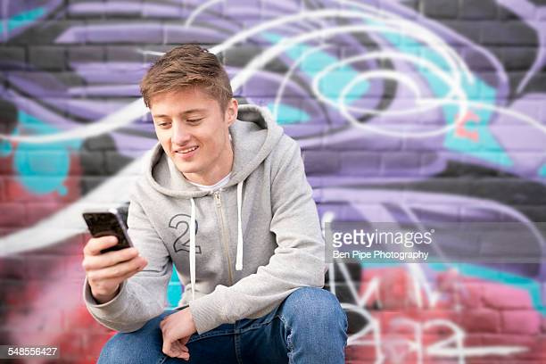 Teenager using smartphone against wall with graffiti