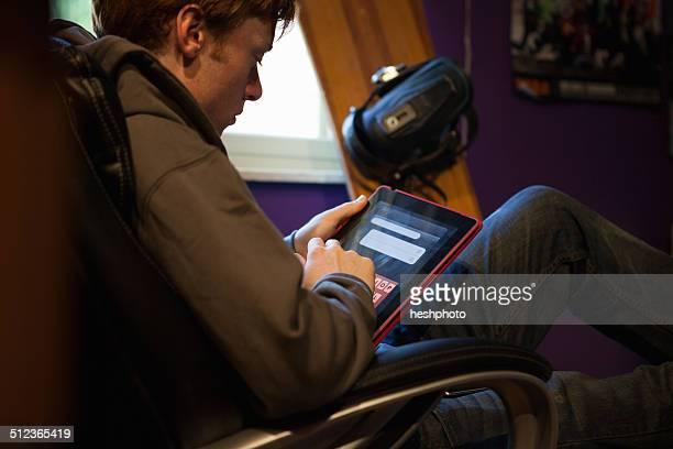 teenager using tablet at home - heshphoto stock-fotos und bilder