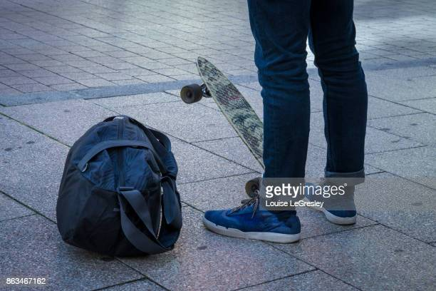 Teenager waiting for the bus with skateboard