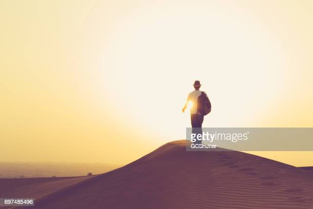 Teenager walking towards the rising sun on the Arabian dunes