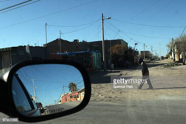 A teenager walks down a road on March 20 2010 in Juarez Mexico The border city of Juarez has been racked by violent drug related crime recently and...