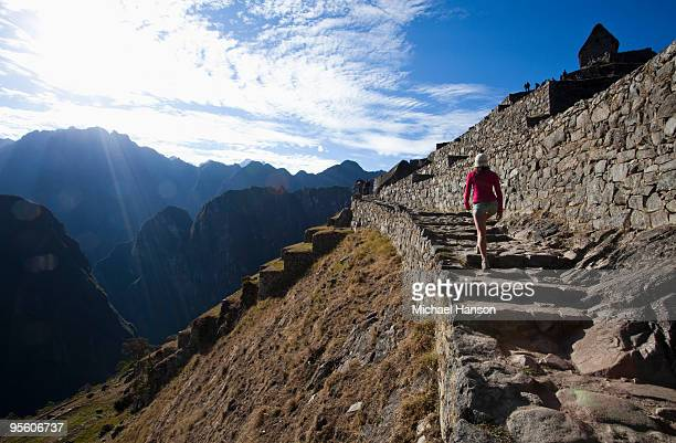 A teenager walks up an ancient staircase overlooking a steep valley as she visits the site of a lost