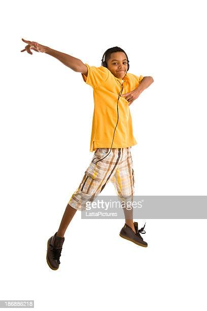 Teenager wearing headset and jumping arms outstretched
