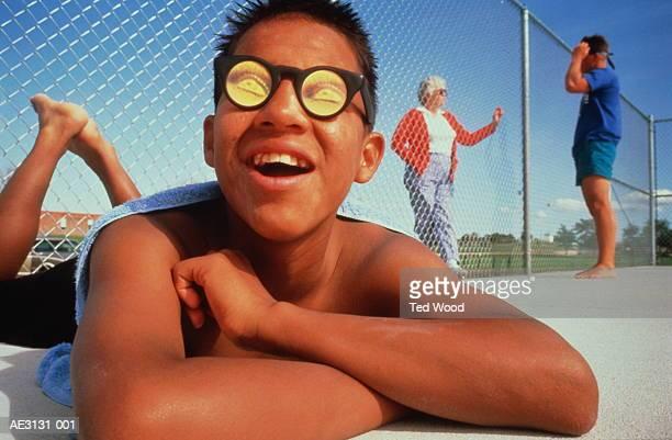 Teenager (14-16) wearing hologram sunglasses, sunbathing