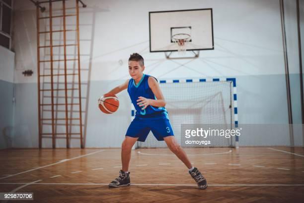Teenager wearing jersey playing basketball indoors