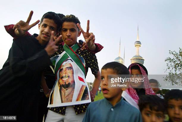 A teenager wears a photograph of Kuwaiti Amir Sheikh Jaber AlAhmad AlJaber AlSabah while celebrating National Day February 25 2003 in Kuwait City...