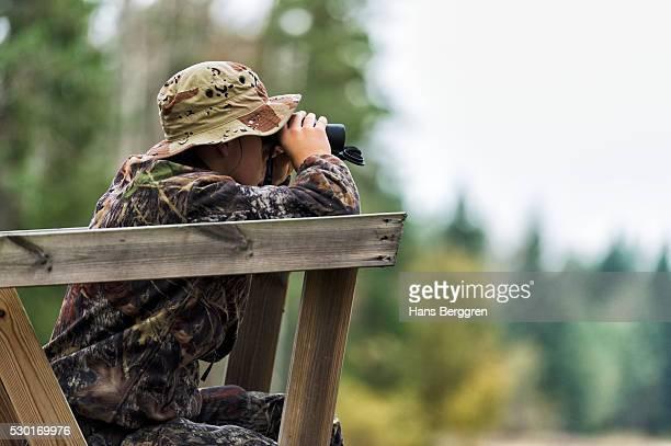 Teenager with binoculars on hunting tower