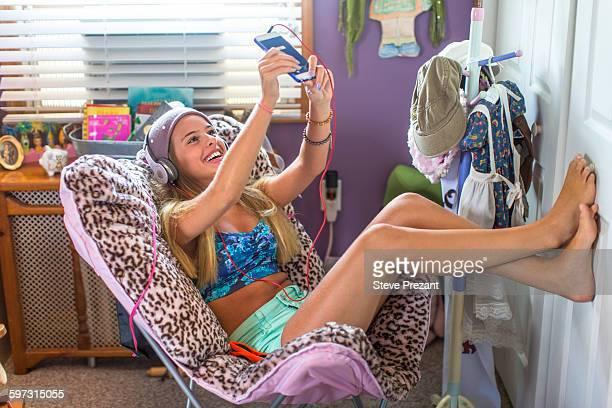 Teenager with earphones taking selfie on lazy chair in bedroom