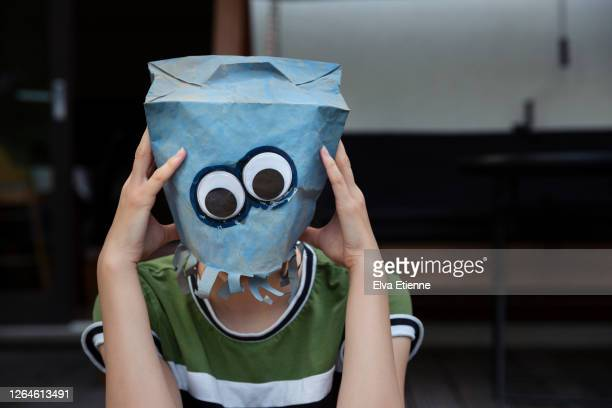 teenager with head in hands whilst wearing a blue painted paper bag and googly eyes over face - offbeat stock pictures, royalty-free photos & images