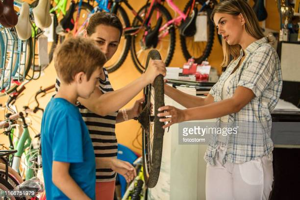 Teenager with his mother buying new bicycle wheel