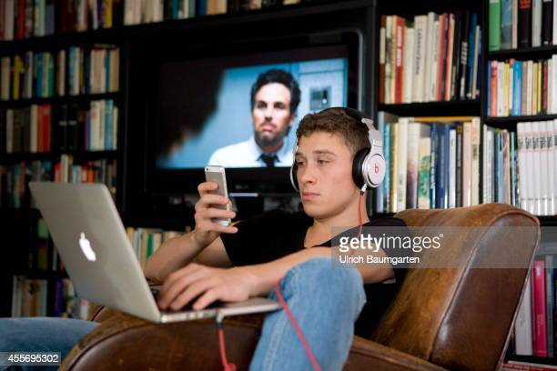 Teenager with laptop, cell phone and headphones in front of running TV and a book wall, on September 18, 2014 in Bonn, Germany.