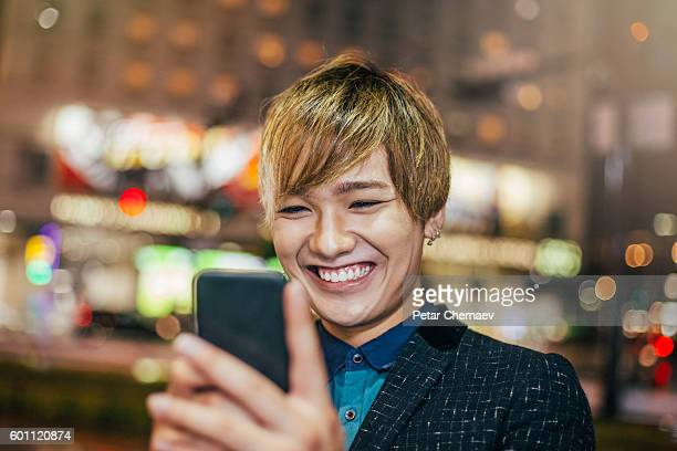 Teenager with smart phone at night