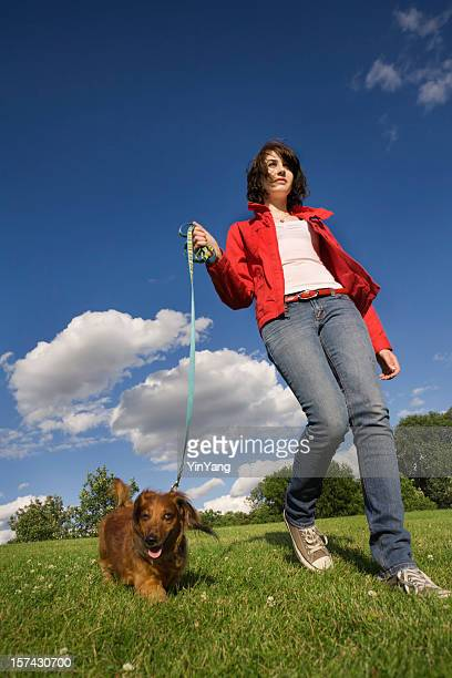 Teenager, Woman Walking Leashed Dachshund Dog Pet on Park Lawn