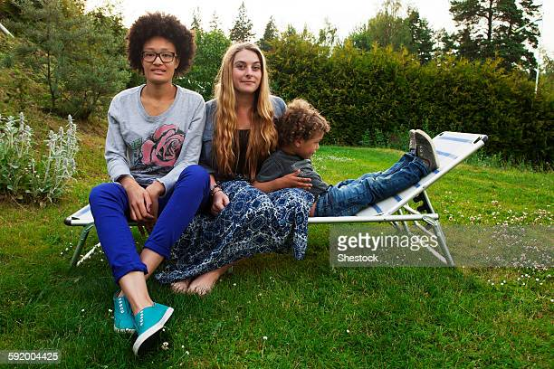 Teenagers and boy relaxing on lawn chair