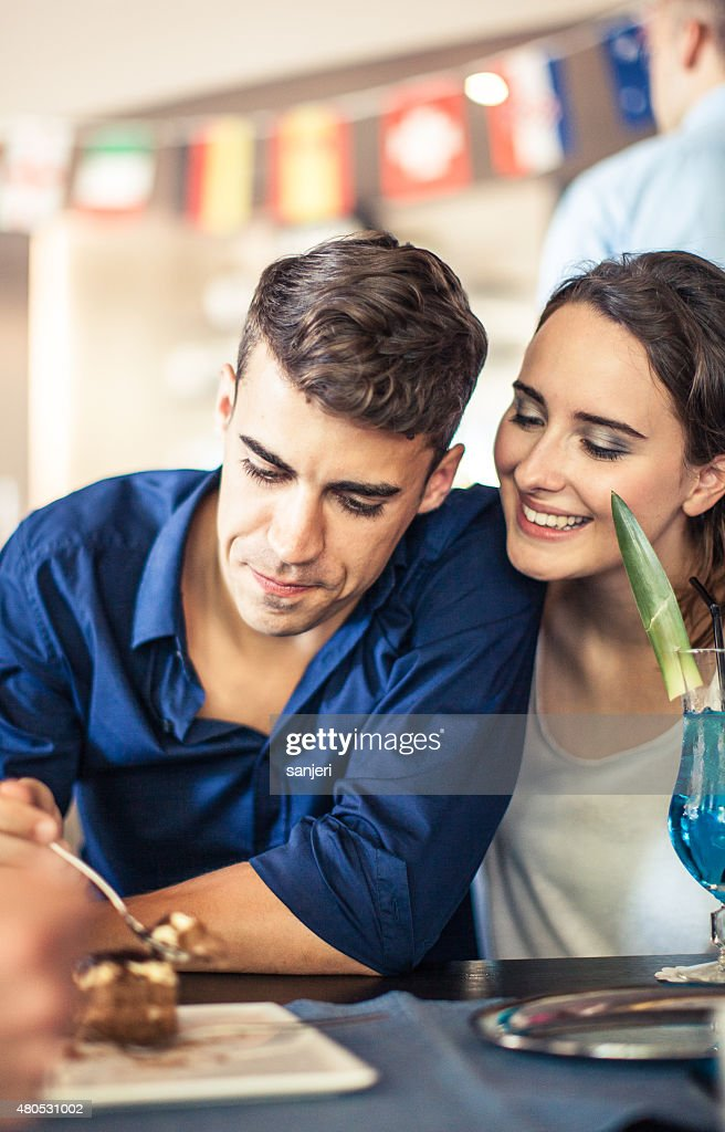Teenagers at the coffee shop eating sweets : Stock Photo