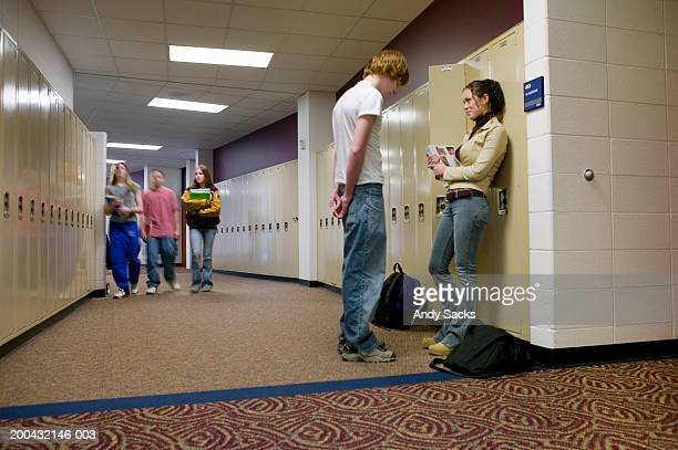 Teenagers (15-17) beside lockers (focus on boy and girl in foreground)