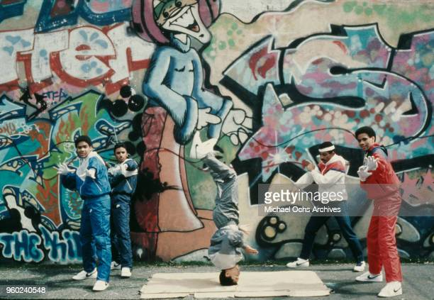 Teenagers breakdancing next to a wall covered in grafitti, Brooklyn, New York, April 1984.