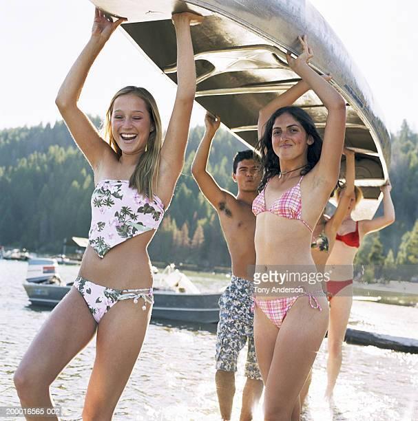 Teenagers (14-16) carrying canoe