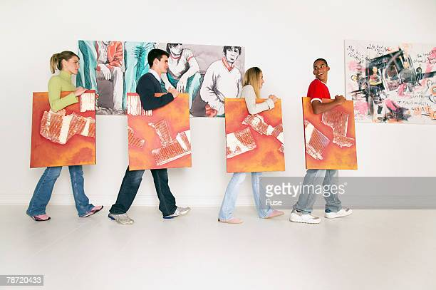 Teenagers Carrying Paintings Through a Gallery