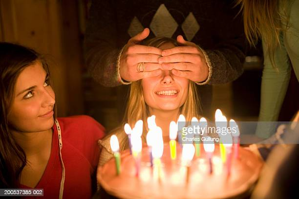 Teenagers (15-18) celebrating birthday with cake and candles
