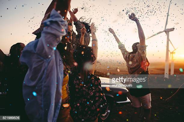 teenagers celebrating with colourful confetti on summer road tri - windenergie stockfoto's en -beelden