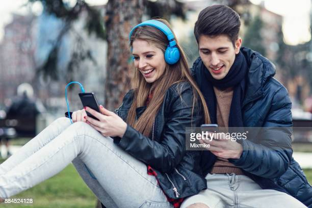 Teenagers chatting on the phone and listening to music