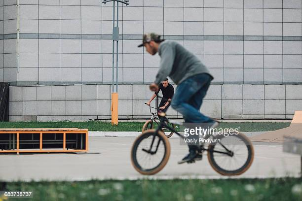 Teenagers cycling at skateboard park