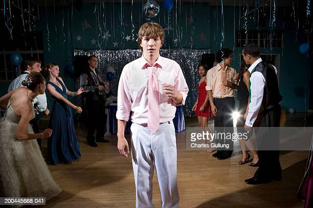 Teenagers (15-18) dancing at prom (focus on boy in foreground)