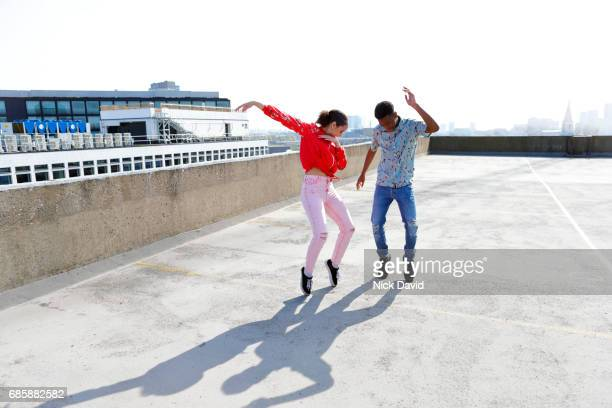 Teenagers dancing on a London rooftop overlooking the city.
