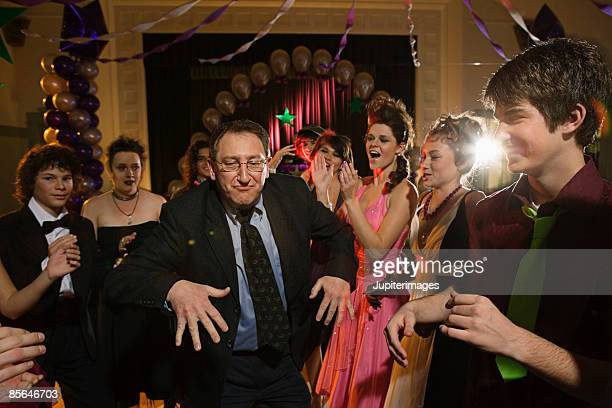 Teenagers dancing with high school principal at prom