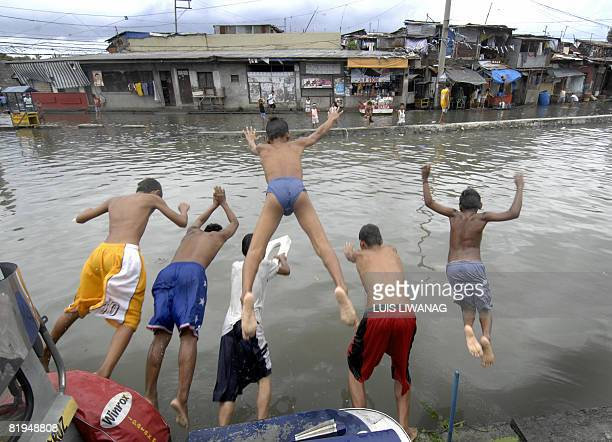Teenagers dive into the rising floodwaters of a floodgate canal in Malabon north of Manila on July 16 2008 Monsoon rains from the tropical storm...